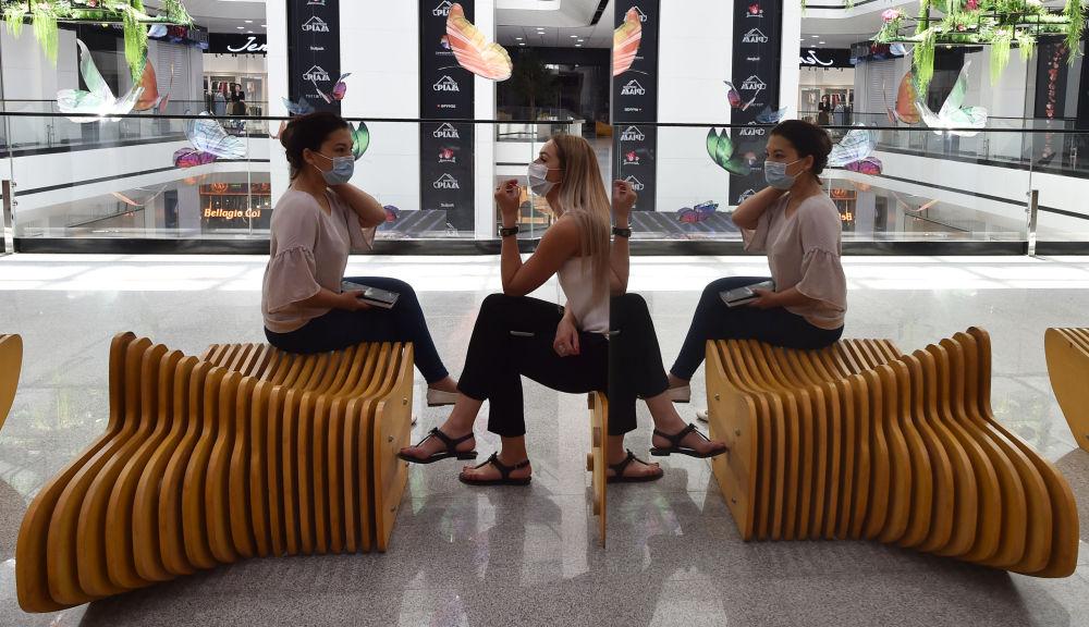 Девушки в лицевых масках разговаривают в торговом центре в Бишкеке, открытые после ослабления мер после ЧП, вызванный новым коронавирусом. 25 мая 2020 года
