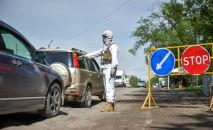 Сотрудник правоохранительных органов на санитарном посту на въезде в Бишкек. Архивное фото