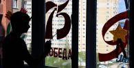Парень красит окно в честь 75-летия Победы в ВОВ. Архивное фото