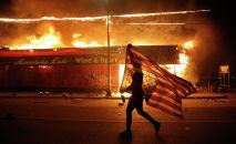 Протестующий несет флаг США вверх ногами, знак бедствия, рядом с горящим зданием в Миннеаполисе. 28 мая 2020 года