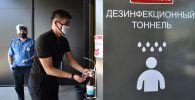 Охранник и посетитель в медицинских масках у входа в торговый центр после ослабления карантинных мер в Бишкеке. 25 мая 2020 года