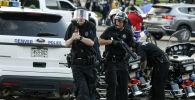 Полицейский направляет пистолет на людей во время акции протеста. Архивное фото
