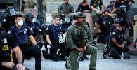 Офицеры стоят на коленях с протестующими во время акции протеста