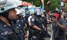 Нью-Йорктогу көчөдө нааразычылык акциясынын учурунда полиция кызматкерлери курчоодо турушат