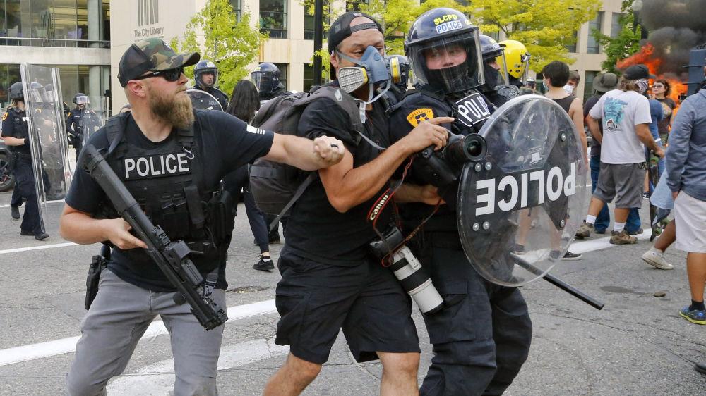 Сүрөтчүнүн иши да оңой эмес. АКШдагы каршылык акциясы учурунда полиция кызматкери фотографты түрткүлөп жатат