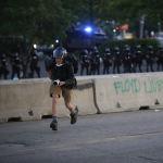 Каршылык акциясы учурунда полициядан качып бараткан сүрөтчү