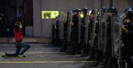 Мужчина встает на колени перед полицейскими во время протеста во время акции протеста против гибели афроамериканца Джорджа Флойда