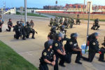Американын Де-Мойн шаарындагы нааразычылык акциясы жүрүп жаткан маалда полиция эл алдында тизелеп турду.