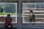 Женщина в защитной маске сидит на автобусной остановке в Бишкеке. Архивное фото