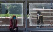 Бишкектеги аялдамада бет кап кийип отурган аял. Архивдик сүрөт