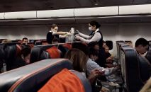 Учактагы стюардессалар жүргүнчүлөргө тамак алып келүүдө. Архивдик сүрөт