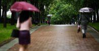 Прохожие гуляют по скверу во время дождя. Архивное фото