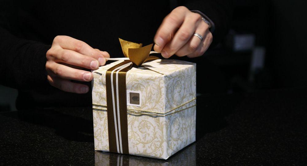 Мужчина держит в руках подарок. Иллюстративное фото