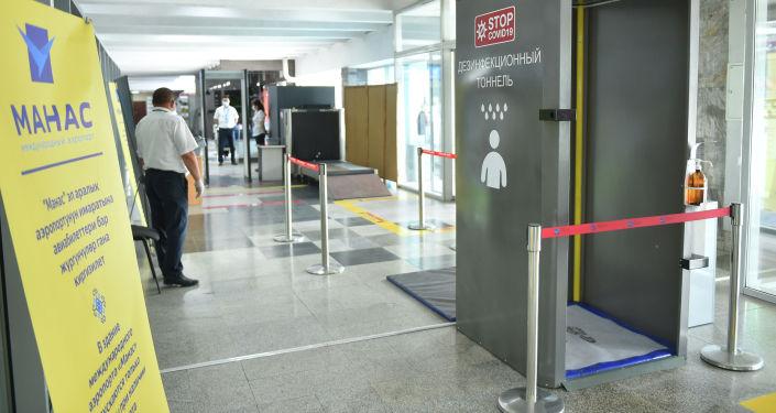 Дезинфекционный тоннель в Международном аэропорту Манас, где идет подготовка к возобновлению внутренних авиарейсов.