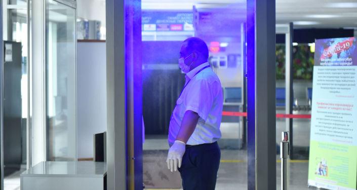 Сотрудник проходит дезинфекцию в тоннеле в Международном аэропорту Манас, где идет подготовка к возобновлению внутренних авиарейсов.