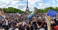 Участники акции протеста против полицейского насилия на Елисейских полях в Париже. Архивное фото