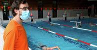 Спасатель в защитной маске контролирует людей, плавающих в общественном бассейне