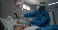 Медицинский работник заботится о пациенте в отделении интенсивной терапии больницы. Архивное фото