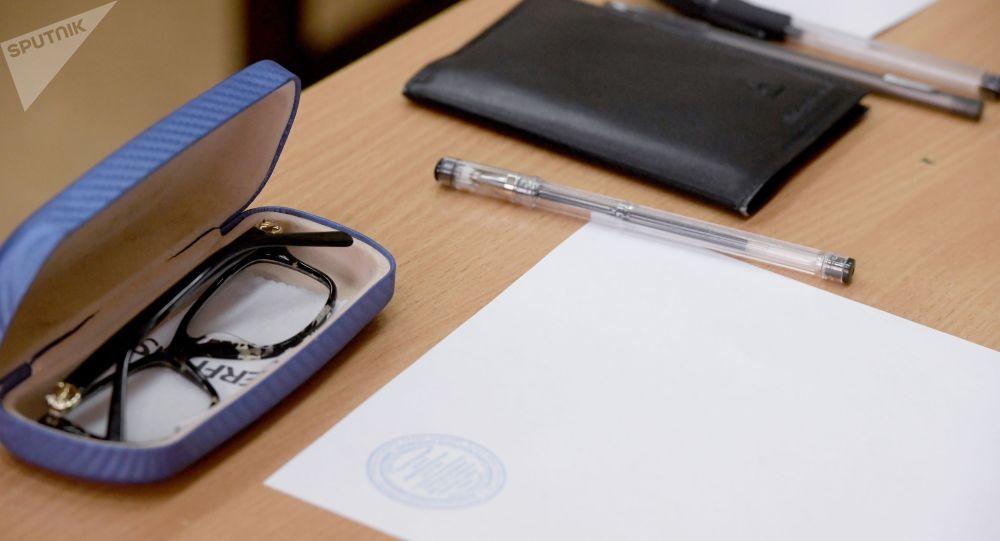 Экзаменге катышкандардын биринин документтери, калемдер жана көз айнек. Архив
