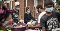 Еду раздают жителям во время раздачи продовольствия. Архивное фото