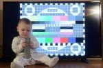 Ребенок с пультом дистанционного управления на фоне телевизионной испытательной таблицы на экране телевизора. Архивное фото
