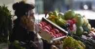 Продавец разговаривает по телефону на продовольственном рынке. Архивное фото