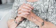 Пожилая женщина держится на руки. Иллюстративное фото
