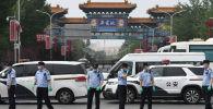 13 июня 2020 года китайская полиция охраняет вход на закрытый рынок Синфади в Пекине.