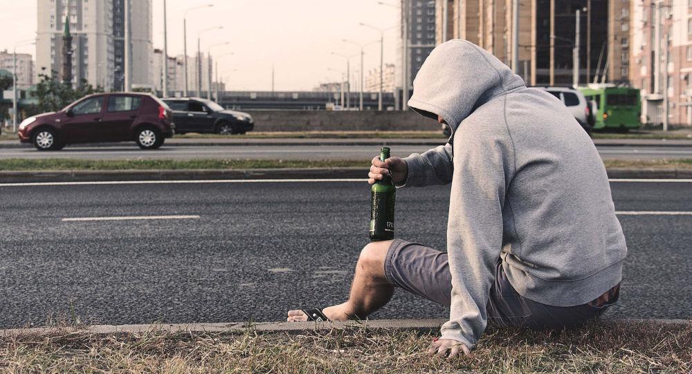 Мужчина держит бутылку пива сидя на обочине. Архивное фото