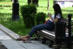 Девушка сидит на скамейке в парке. Архивное фото