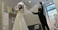 Девушка примеряет платье в свадебном салоне. Архивное фото