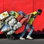 Мужчины везут тележку с товарами в Тегусигальпе (Гондурас)