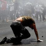 Мужчина пытается встать после удара водяной пушкой во время акции протеста возле резиденции премьер-министра в Катманду (Непал). Протестующие требуют от правительства более эффективных мер борьбы с COVID-19 и ростом числа зараженных.