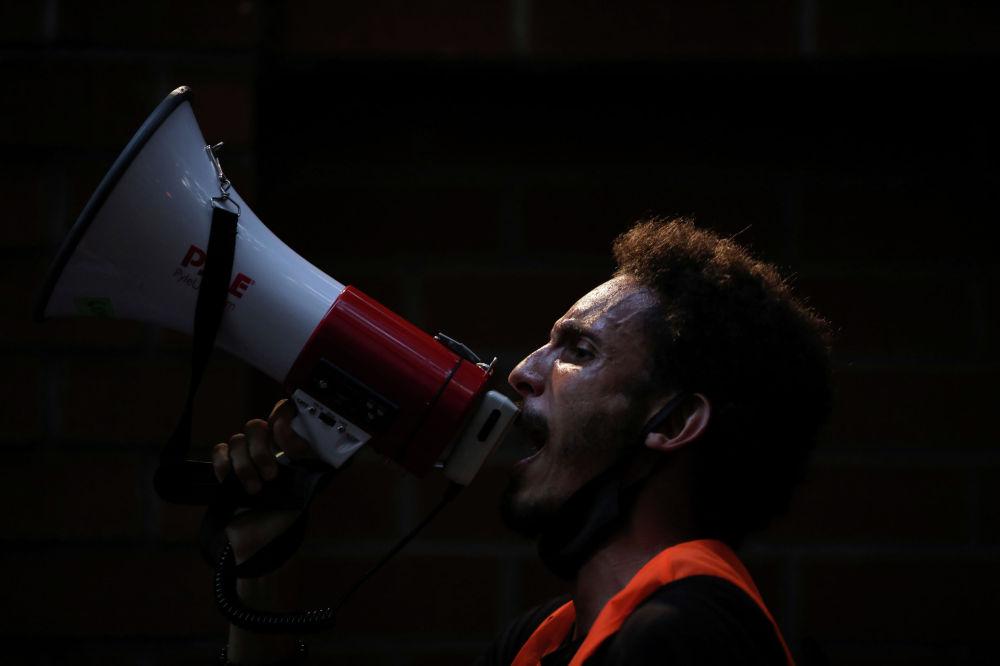Демонстрант в Нью-Йорке (США) возглавляет митинг против жестокости полиции и расового неравенства после смерти Джорджа Флойда