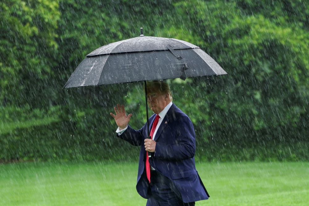 Президент США Дональд Трамп машет репортерам с лужайки Белого дома