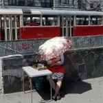 Уличная продавщица укрывается зонтом от солнца в Киеве (Украина)