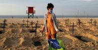 Активистка НПО Рио-де-Пас на демонстрации, во время которой на пляже Копакабана было выкопано сто могил, символизирующих умерших от COVID-19 в Рио-де-Жанейро (Бразилия)