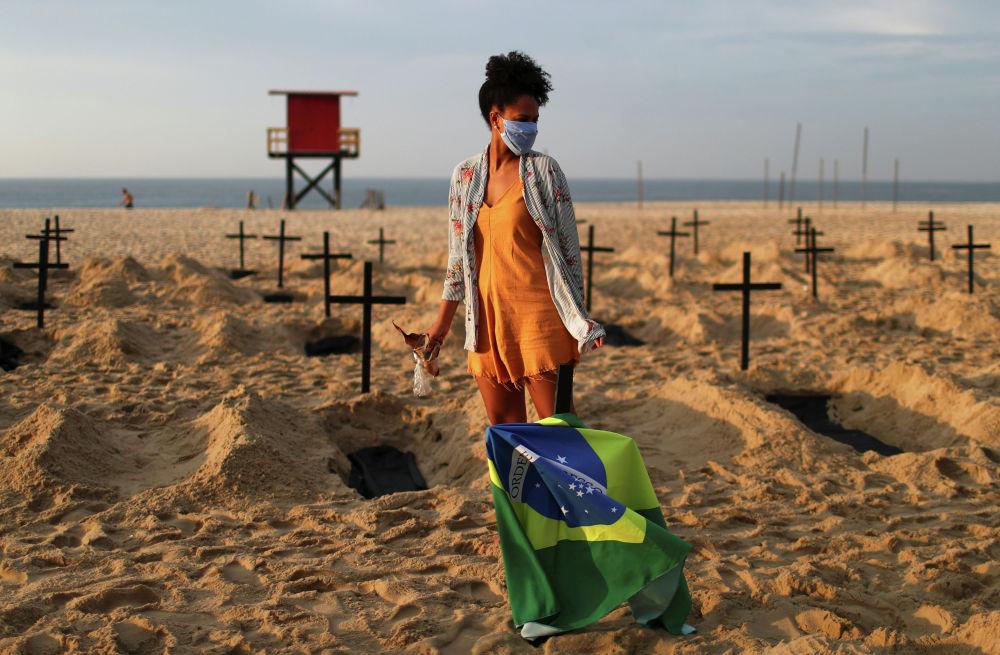Активистка НПО Рио-де-Пас на демонстрации, во время которой на пляже Копакабана в Рио-де-Жанейро (Бразилия) выкопали сто могил, символизирующих умерших от COVID-19