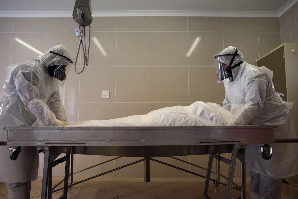 Члены мусульманской организации в Кейптауне (ЮАР) готовят к захоронению тело человека, который умер от COVID-19