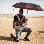 Житель Сенегала опускается на одно колено во время акции протеста в знак солидарности с движением Black Lives Matter
