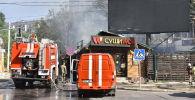Сотрудники МЧС на месте крупного пожара в точке быстрого питания и находящейся рядом аптеке по улице Сухэ-Батора в Бишкеке