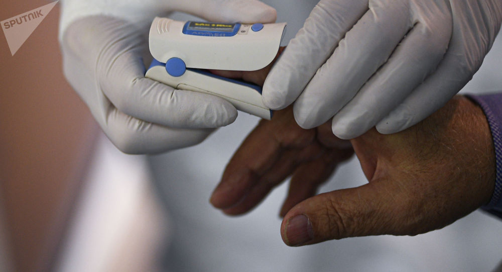Врач надевает датчик на руку пациента. Архивное фото
