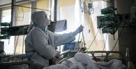 Врач проверяет капельницу у пациента в реанимации. Архивное фото