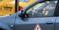 Начинающий водитель во время практических занятий в автошколе. Архивное фото