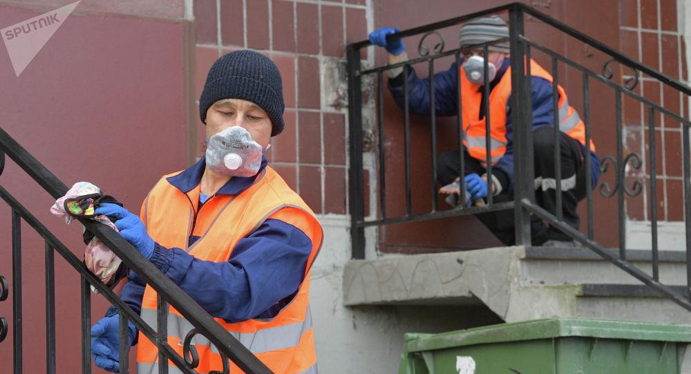 Сотрудники коммунальной службы проводят санитарную обработку парадной в Санкт-Петербурге. Архивное фото