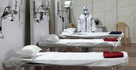Женщина в защитном костюме стоит рядом с кроватями в больнице. Архивное фото