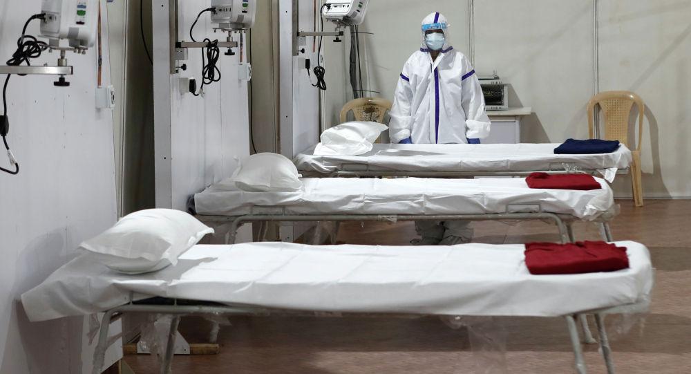 Женщина в защитном костюме стоит рядом с кроватями в больнице. Архивное фотоЗа сутки от COVID вылечились 32 кыргызстанца — заразилось в 3 раза больше