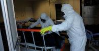 Похоронные работники забирают тело человека. Архивное фото