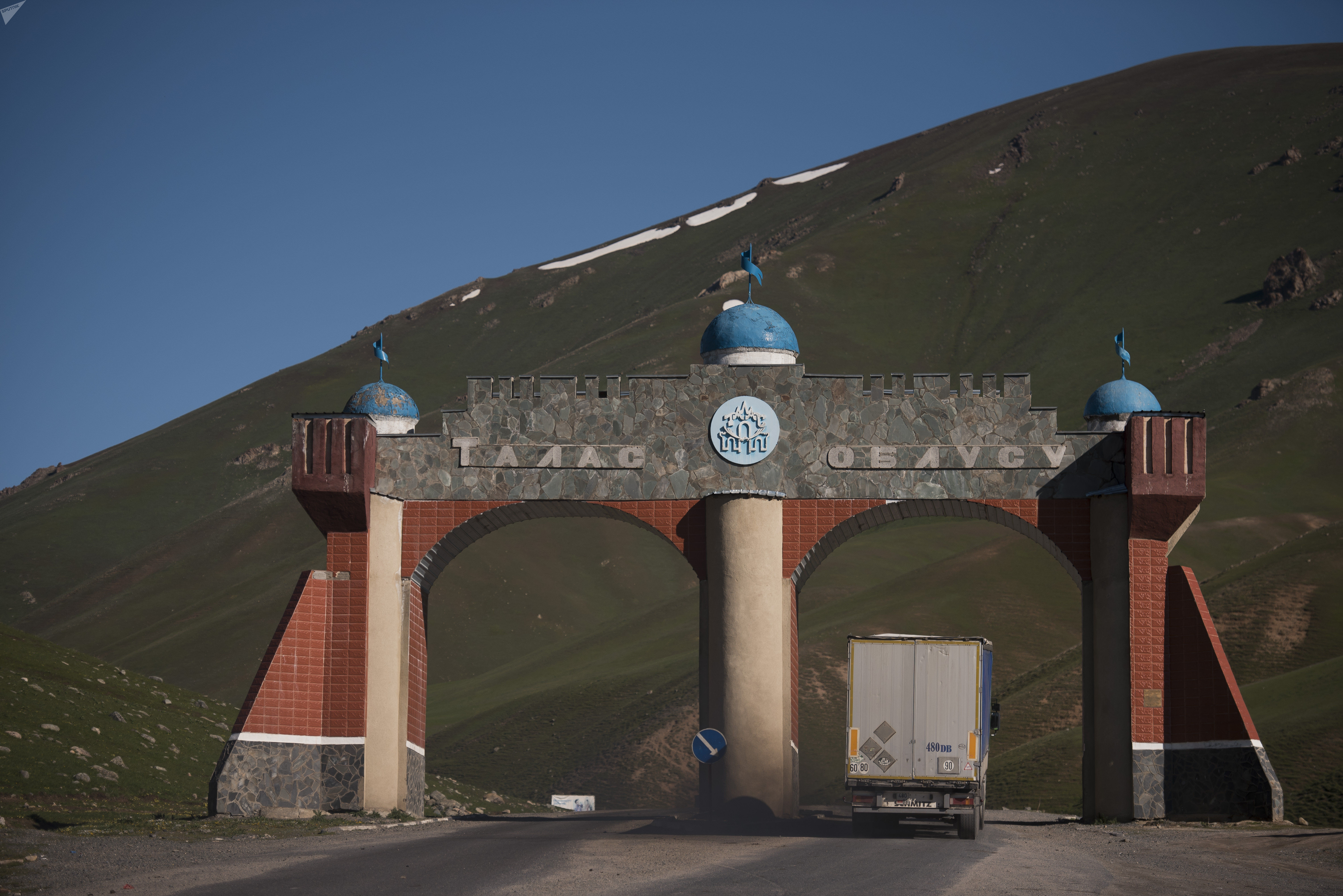 Большегрузная фура проезжает арку на автодороге в Таласской области