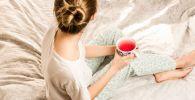 Женщина с чашкой сидит на кровати. Иллюстративное фото